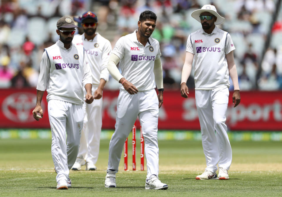 India's Umesh Yadav, centre, reacts after suffering an injury while bowling during play on day three of the second cricket test between India and Australia at the Melbourne Cricket Ground, Melbourne, Australia, Monday, Dec. 28, 2020. (AP Photo/Asanka Brendon Ratnayake)