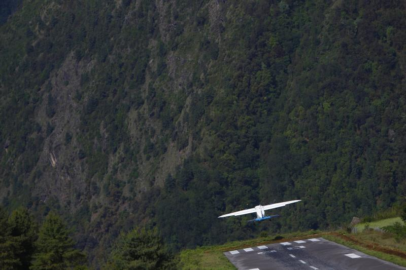 In this Sunday, May 26, 2013 photo, a flight takes off for Katmandu from Lukla airport, Nepal. Carved out of side of a mountain, the airport was built by Sir Edmund Hillary in 1965, and at an altitude of 2,843 meters (9,325 feet) the Lukla airport has earned the reputation of being one of the most extreme and dangerous airports in the world. (AP Photo/Niranjan Shrestha)