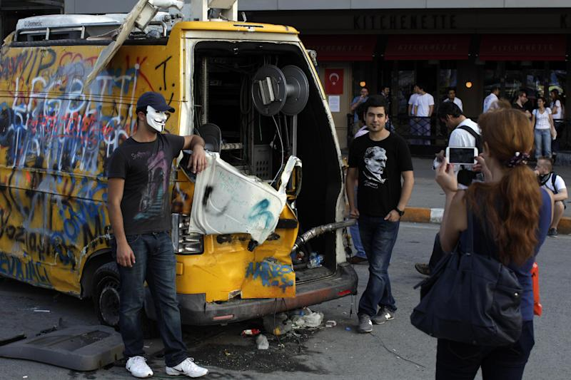 Protesters pose for a picture in front of a destroyed TV van at Taksim square in Istanbul, Tuesday, June 4, 2013. As Turkey's largest city was convulsed by some of the most widespread anti-government protests the country has seen in modern times, the country's broadcast media looked away. Dense clouds of acrid, choking tear gas might have been blanketing the central square of Turkey's largest city, but it was penguins that were the theme of the evening on one of the country's largest private television stations. Its nature documentary ran uninterrupted, while another channel opted for a cooking show and a documentary on Adolf Hitler. (AP Photo/Kostas Tsironis)
