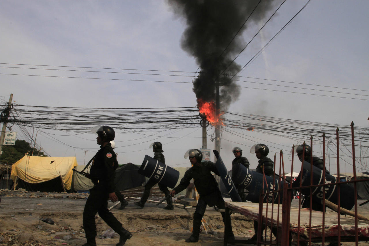 Cambodian riot police officers walk past a burning electric wire as they head to block garment workers on strike near a factory of Canadia Center, on the Stung Meanchey complex at the outskirt of Phnom Penh, Cambodia, Friday, Jan. 3, 2014. Police wounded several striking Cambodian garment workers Friday when they opened fire to break up a labor protest, witnesses said.(AP Photo/Heng Sinith)
