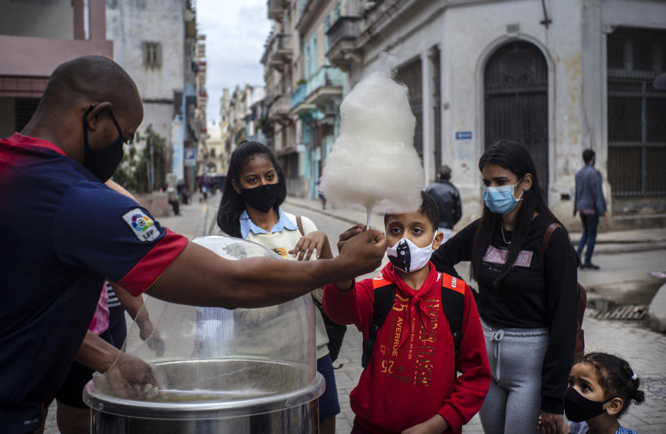 FILE - In this Jan. 11, 2021 file photo, people wearing masks as a precaution against the spread of the new coronavirus wait for their turn to buy cotton candy in Havana, Cuba. In 2021, the government is implementing a deep financial reform that reduces subsidies, eliminates a dual currency that was key to the old system, and raises salaries, in hopes of boosting productivity to help alleviate an economic crisis and reconfigure a socialist system that will still grant universal benefits such as free health care and education. (AP Photo/Ramon Espinosa, File)
