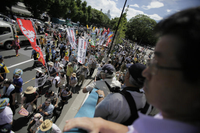 """Anti-nuclear energy protesters march through downtown Tokyo Monday, July 16, 2012. Tens of thousands of people gathered at a Tokyo park, demanding """"Sayonara,"""" or goodbye, to nuclear power as Japan prepares to restart yet another reactor, and expressed outrage over a report that blamed culture on the Fukushima disaster. (AP Photo/Greg Baker)"""
