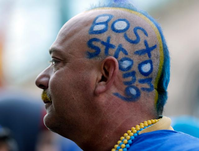 """Mike Poitras, of Dracut, Mass., wears the slogan """"Boston Strong"""" on his head near the finish line before the start of 118th Boston Marathon Monday, April 21, 2014 in Boston. (AP Photo/Charles Krupa)"""