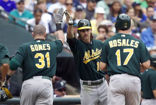 Oakland Athletics' Josh Reddick, center, congratulates teammate Jonny Gomes, left, after Gomes hit a three-run home run in the fifth inning of a baseball game against the Seattle Mariners at Safeco Field in Seattle, Sunday, Sept 9, 2012. Athletics' Adam Rosales, right, who also scored, looks on. (AP Photo/Stephen Brashear)