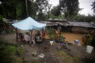 A family stand outside their home damaged by a flooding caused by rains from Storm Eta, in Tela