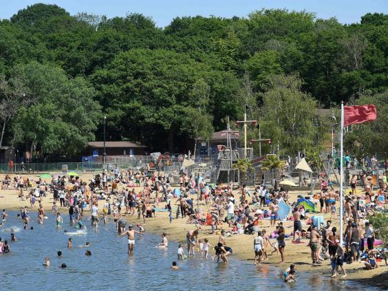 People enjoy the sunshine in the water and on the beach at Ruislip Lido in west London on Saturday (JUSTIN TALLIS/AFP via Getty Images)