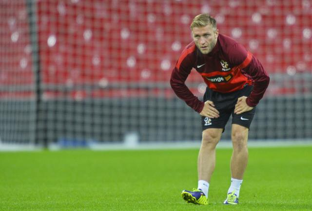 Poland's captain Jakub Blaszczykowski stretches during a training session ahead of their 2014 World Cup qualifying soccer match against England, at Wembley Stadium in west London October 14, 2013. REUTERS/Toby Melville (BRITAIN - Tags: SPORT SOCCER)
