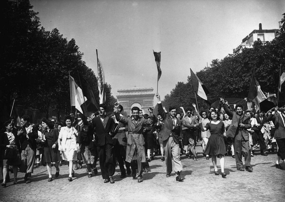 <p>Crowds filled with both servicemen and civilians celebrate the defeat by marching down the Champs Élysées waving banners and flags. </p>