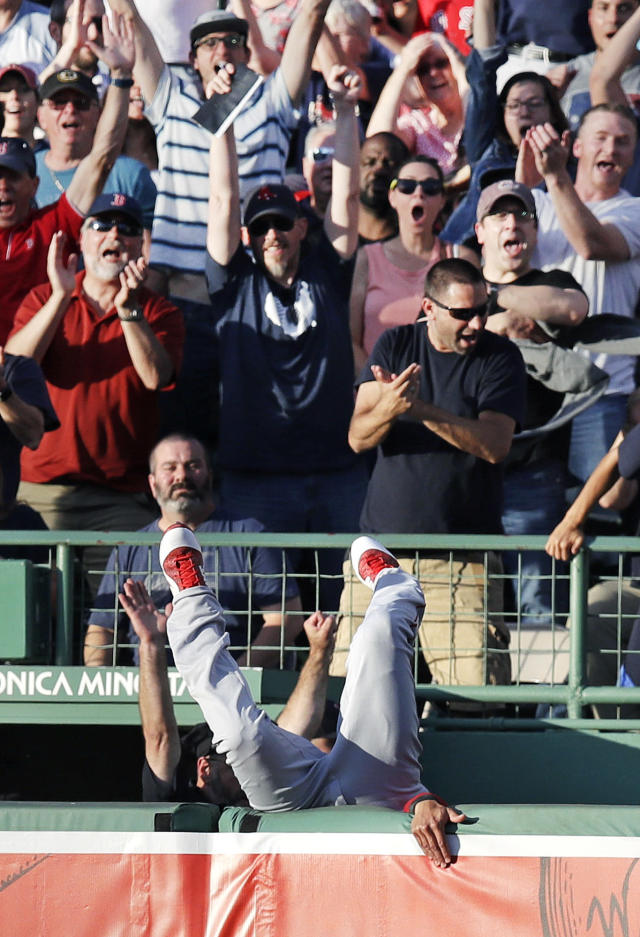 Los Angeles Angels center fielder Michael Hermosillo flips over the bullpen wall while chasing a home run hit by Boston Red Sox's Mookie Betts during the first inning of a baseball game at Fenway Park in Boston, Tuesday, June 26, 2018. (AP Photo/Charles Krupa)