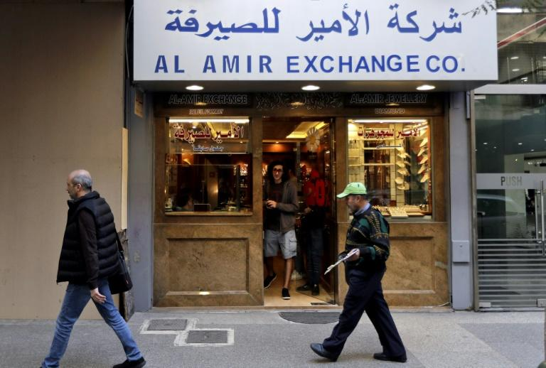 People walk past a money exchange office in the Lebanese capital Beirut