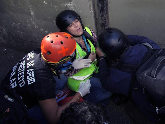 A journalist working for CNN is assisted after being injured in clashes between demostrators and mlitary police during a protest against the 2014 World Cup, in Sao Paulo June 12, 2014. Brazilian police and protesters clashed in Sao Paulo on Thursday just hours before the opening game of the World Cup, which has been marred by construction delays and months of political unrest. Police fired tear gas and noise bombs to disperse more than 100 demonstrators angry about heavy government spending on the event, a spokesman for Sao Paulo state's military police said. REUTERS/Stringer/Brazil (BRAZIL - Tags: SPORT SOCCER WORLD CUP CIVIL UNREST POLITICS MEDIA)