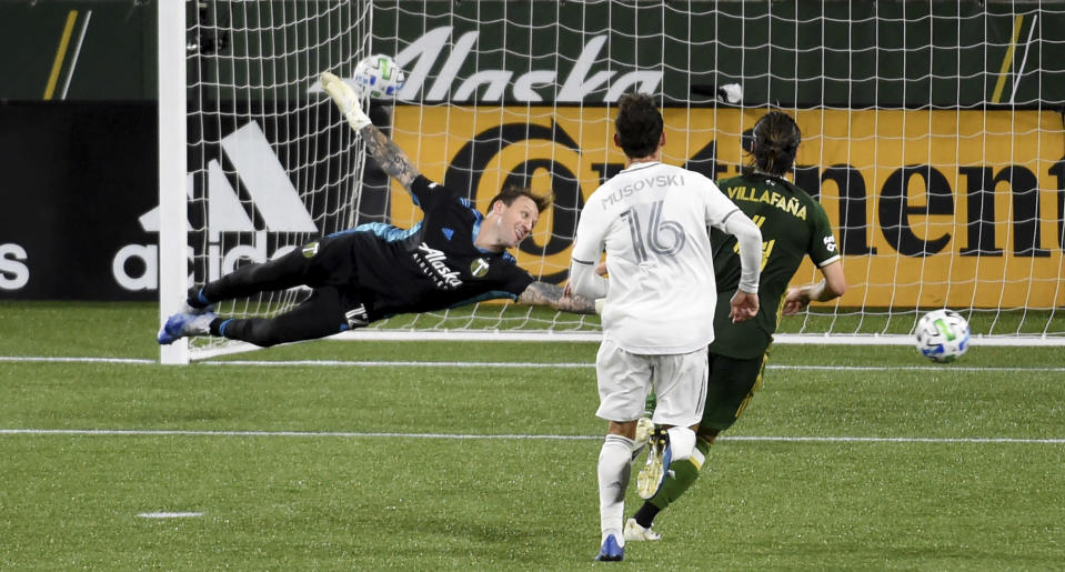 Portland Timbers goalkeeper Steve Clark, left, has the ball go by him for a goal in stoppage time as Los Angeles FC forward Danny Musovski, center, and Portland Timbers defender Jorge Villafana, right, look on during the second half of an MLS soccer match in Portland, Ore., Sunday, Oct. 18, 2020. The match ended in a 1-1- draw. (AP Photo/Steve Dykes)