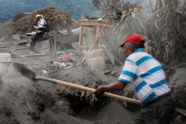 """Eufemia Garcia, 48, who lost 50 members of her family during the eruption of the Fuego volcano, observes a volunteer who is aiding her in the search for her family in San Miguel Los Lotes in Escuintla, Guatemala, June 11, 2018. REUTERS/Carlos Jasso SEARCH """"EUFEMIA MISSING"""" FOR THIS STORY. SEARCH """"WIDER IMAGE"""" FOR ALL STORIES. TPX IMAGES OF THE DAY."""