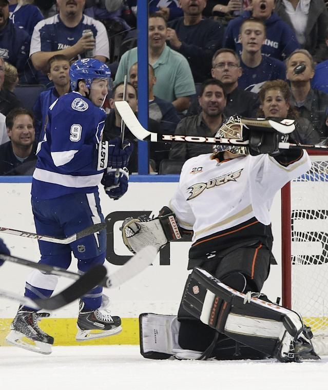 Anaheim Ducks goalie Jonas Hiller, right, makes a blocker-save on a shot by Tampa Bay Lightning center Tyler Johnson (9) during the first period of an NHL hockey game on Thursday, Nov. 14, 2013, in Tampa, Fla. (AP Photo/Chris O'Meara)