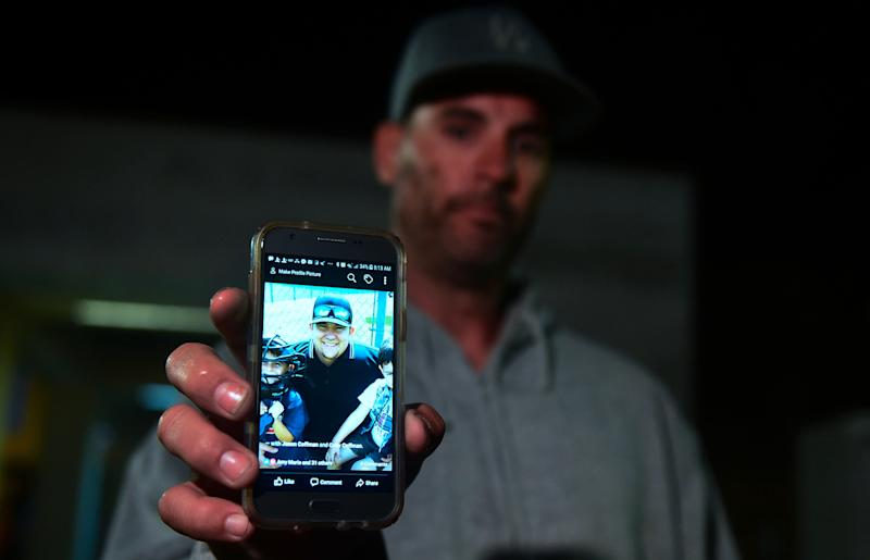 Jason Coffman displays a photo of his son Cody outside the Thousands Oaks Teen Center, where he came hoping to find his son who was at the Borderline Bar & Grill.