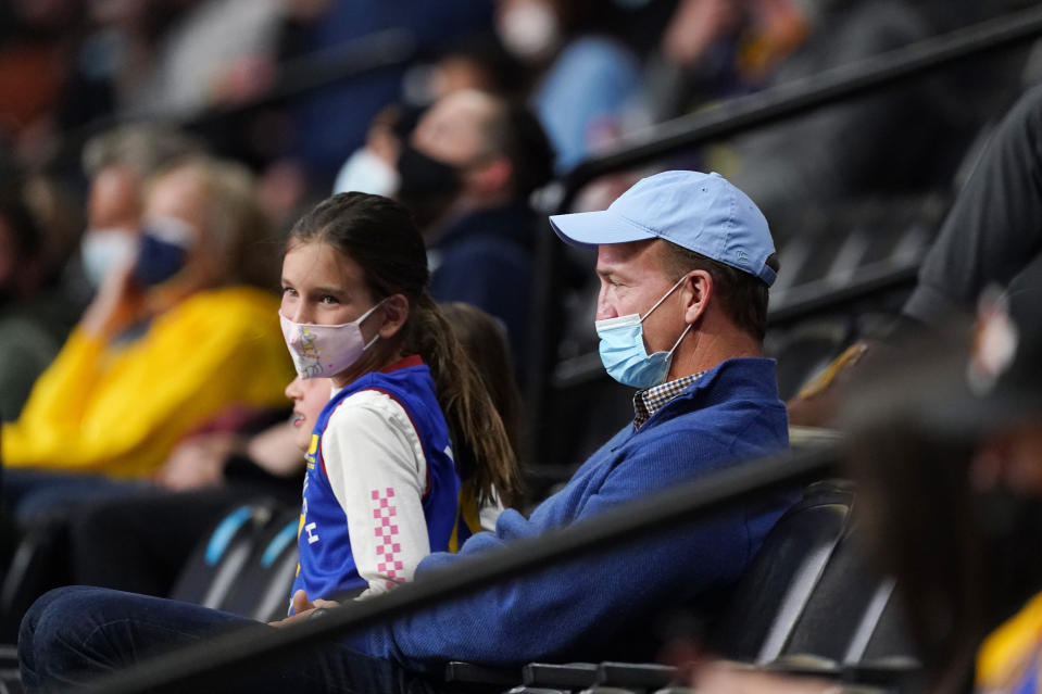 Retired Denver Broncos quarterback Peyton Manning looks on as the Memphis Grizzlies face the Denver Nuggets in the first half of an NBA basketball game Monday, April 19, 2021, in Denver. (AP Photo/David Zalubowski)