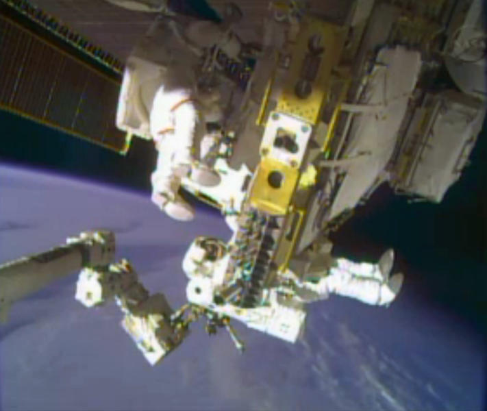 CORRECTS DAY OF WEEK TO TUESDAY INSTEAD OF MONDAY - In this image taken from video provided by NASA, astronauts Rick Mastracchio, top, and Michael Hopkins work to repair an external cooling line on the International Space Station on Tuesday, Dec. 24, 2013, 260 miles above Earth. The external cooling line — one of two — shut down Dec. 11. The six-man crew had to turn off all nonessential equipment, including experiments. (AP Photo/NASA)