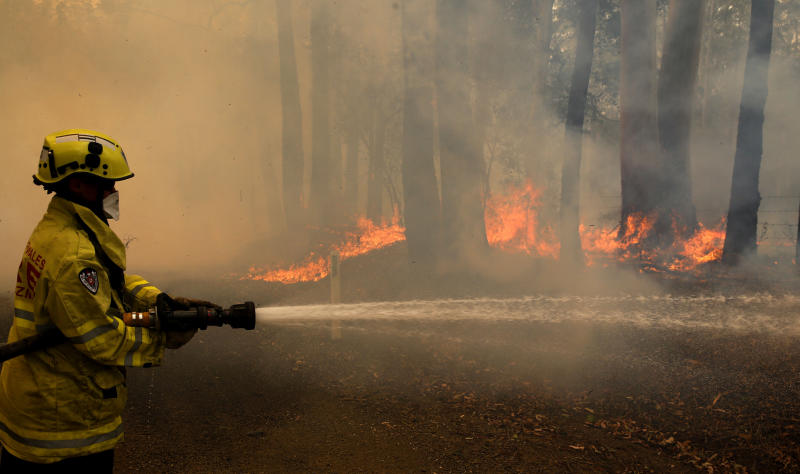 A Gloucester fire crew member fights flames at Koorainghat on Tuesday as the fires worsen across NSW.
