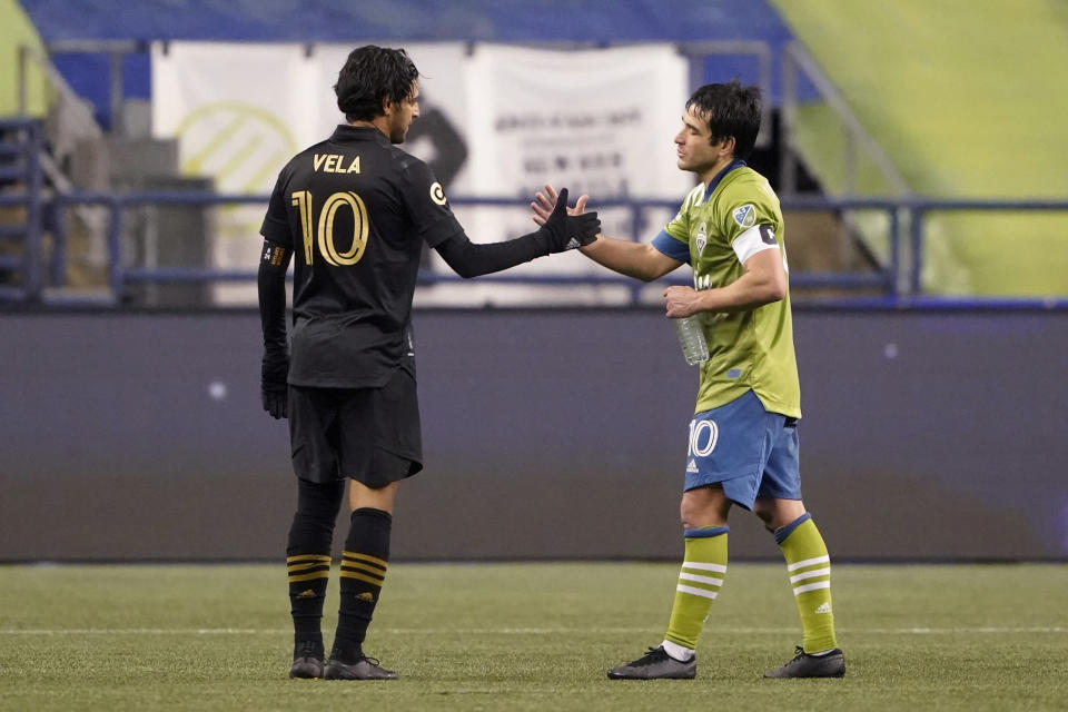 Seattle Sounders midfielder Nicolas Lodeiro, right, greets Los Angeles FC forward Carlos Vela after an MLS playoff soccer match Tuesday, Nov. 24, 2020, in Seattle. The Sounders won 3-1. (AP Photo/Ted S. Warren)