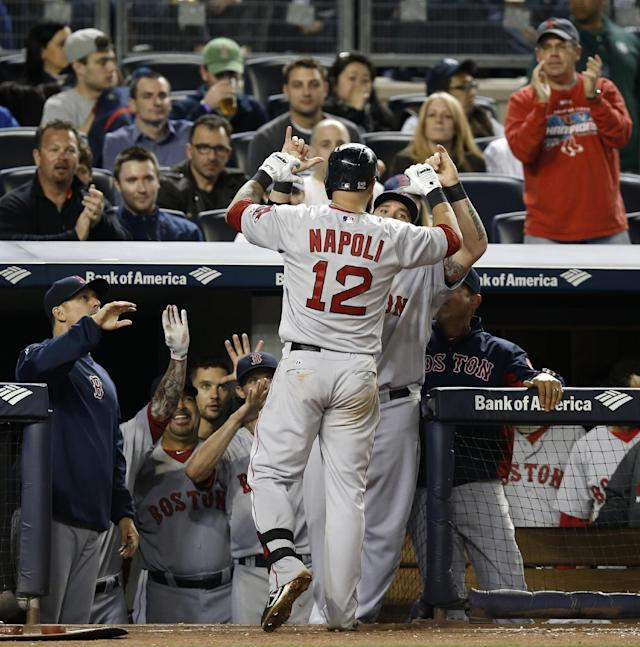 Teammates congratulate Boston Red Sox Mike Napoli (12) after he hit a sixth-inning solo home run off New York Yankees starting pitcher Ivan Nova in a baseball game at Yankee Stadium in New York, Sunday, April 13, 2014. (AP Photo/Kathy Willens)