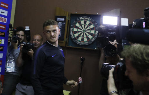 England's Kieran Trippier looks back after getting the darts from the board as he plays an impromptu game with a member of the media before speaking to journalists at the England media centre in Repino, near St Petersburg, Russia at the 2018 soccer World Cup, Thursday, June 21, 2018. (AP Photo/Alastair Grant)