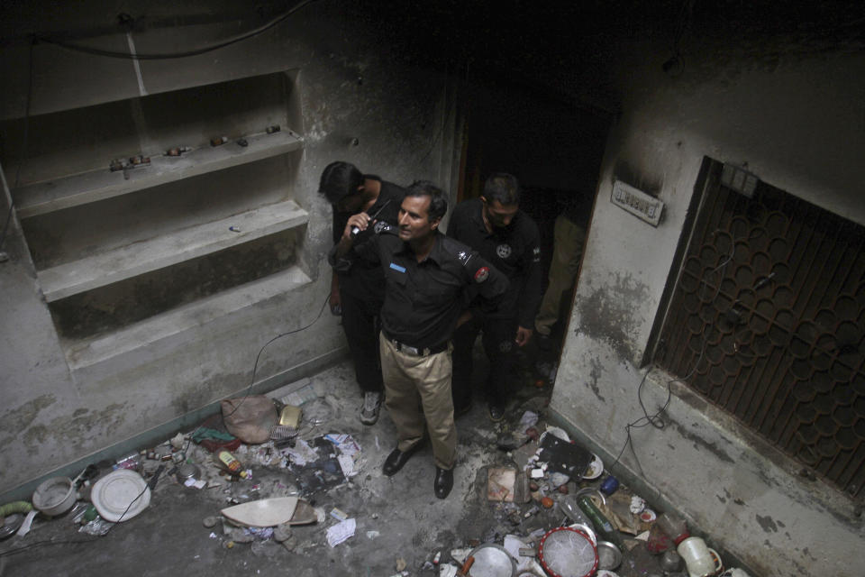 FILE - In this Monday, July 28, 2014 file photo, Pakistani police officers examine a house of a family belonging to the Ahmadi sect, which was torched by angry mob following rumors about blasphemous postings on Facebook, in Gujranwala, Pakistan. The U.S. Commission on International Religious Freedom on Friday, Jan. 8, 2021, adopted 55-year-old Ramazan Bibi, jailed on blasphemy charges in Pakistan, as a prisoner of conscience. According to a December report by the U.S. Commission for International Religious Freedoms, Pakistan recorded the most cases of blasphemy in the world even though 84 countries have criminal blasphemy laws on their books. (AP Photo/K.M. Chaudary, File)