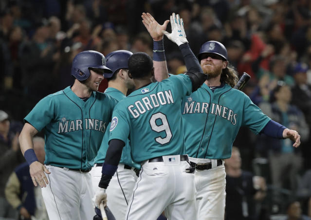 Seattle Mariners' Ben Gamel, right, high-fives Dee Gordon (9) after Gamel scored on a go-ahead two-run double by Denard Span against the Boston Red Sox during the eighth inning of a baseball game Friday, June 15, 2018, in Seattle. The Mariners won 7-6. (AP Photo/Ted S. Warren)