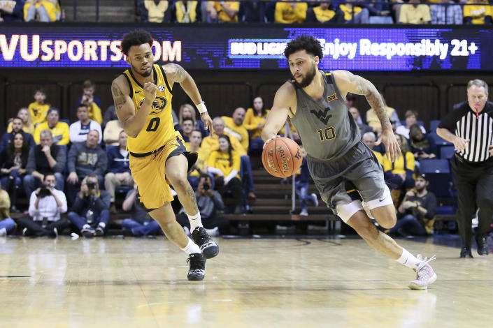 West Virginia guard Jermaine Haley (10) drives it up court as he is defended by Missouri guard Torrence Watson (0) during the second half of an NCAA college basketball game Saturday, Jan. 25, 2020, in Morgantown, W.Va. (AP Photo/Kathleen Batten)