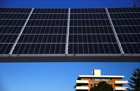 FILE PHOTO: A solar array, a linked collection of solar panels, can be seen in front of a residential apartment block in the Sydney suburb of Chatswood in Australia