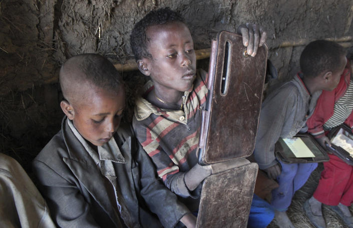 In this photo taken Tuesday, Nov. 27, 2012, Kelbesa Negusse, center, looks at a tablet computer given to the children by the One Laptop Per Child project in the village of Wenchi, Ethiopia. The project gave tablets to the children in the poor, illiterate village to see how much the children could teach themselves and now many kids can recite the English alphabet and spell words in English. (AP Photo/Jason Straziuso)