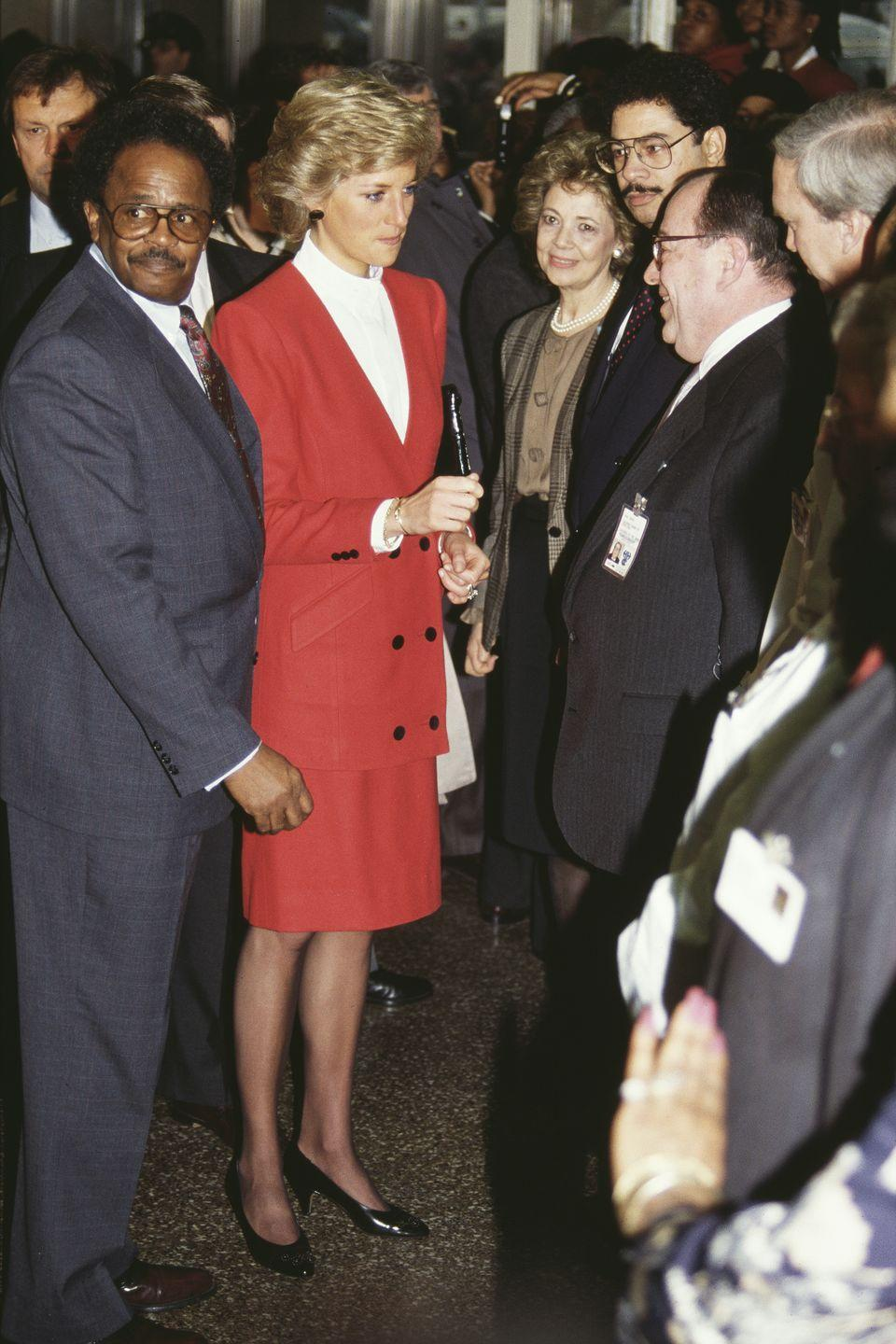 "<p>The princess wears a red Catherine Walker skirt suit while visiting the AIDS unit at Harlem Hospital. She <a href=""https://apnews.com/article/86aba3240f517c4c63b49674c0555f7c"" rel=""nofollow noopener"" target=""_blank"" data-ylk=""slk:met several children"" class=""link rapid-noclick-resp"">met several children</a> suffering from the illness before ending her trip to New York. </p>"