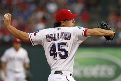 Texas Rangers' Derek Holland (45) delivers to the Chicago White Sox in the first inning of a baseball game on Saturday, April 7, 2012, in Arlington, Texas. (AP Photo/Tony Gutierrez)