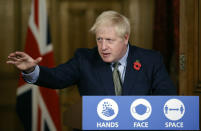 """FILE - In this Nov. 9, 2020 file photo Britain's Prime Minister Boris Johnson reaches out during a virtual press conference on the coronavirus pandemic at 10 Downing Street in central London. Johnson is self-isolating after being told he came into contact with someone who tested positive for the coronavirus, officials said Sunday Nov. 15. """"He will carry on working from Downing Street, including on leading the government's response to the coronavirus pandemic,"""" a statement from his office said. (Tolga Akmen / Pool via AP, File)"""