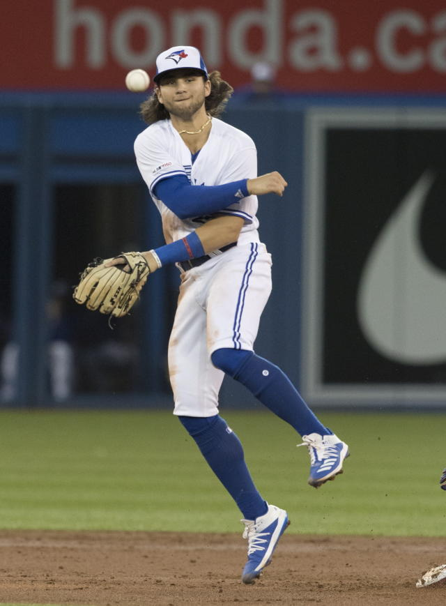 Toronto Blue Jays shortstop Bo Bichette throws to first after forcing out Boston Red Sox's Chris Owings, but fails to turn the double play in the second inning of a baseball game Tuesday, Sept. 10, 2019, in Toronto. Marco Hernandez was safe at first. (Fred Thornhill/The Canadian Press via AP)