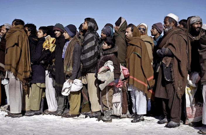Internally displaced Afghans wait in line to receive firewood donated by Welt Hunger Hilfe 'German Agro Action' in Kabul, Afghanistan, Sunday, Dec. 30, 2012. Around 240 internally displaced families received firewood. (AP Photo/Musadeq Sadeq)