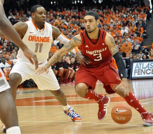 Louisville's Peyton Silva, right, drives against Syracuse's Scoop Jardine during the first half of an NCAA college basketball game in Syracuse, N.Y., Saturday, March 3, 2012. (AP Photo/KevinRivoli)