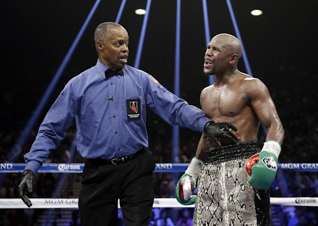 Floyd Mayweather speaks to referee Kenny Bayless after claiming Marcos Maidana bit him. (AP)