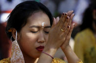 A Balinese woman prays at a temple amid concerns of the new coronavirus outbreak during a Hindu ritual in Bali, Indonesia Saturday, July 4, 2020. (AP Photo/Firdia Lisnawati)