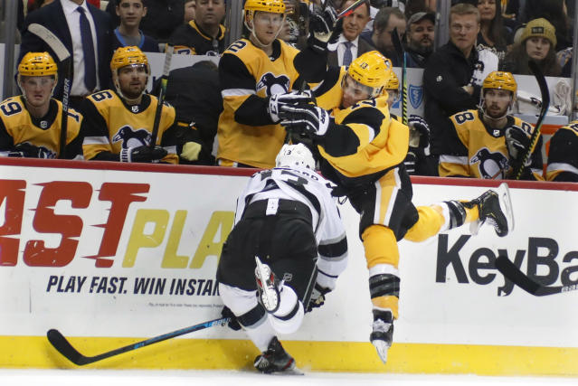 Pittsburgh Penguins' Brandon Tanev, right, jumps as he avoids a check by Los Angeles Kings' Kyle Clifford during the second period of an NHL hockey game, Saturday, Dec. 14, 2019, in Pittsburgh. (AP Photo/Keith Srakocic)