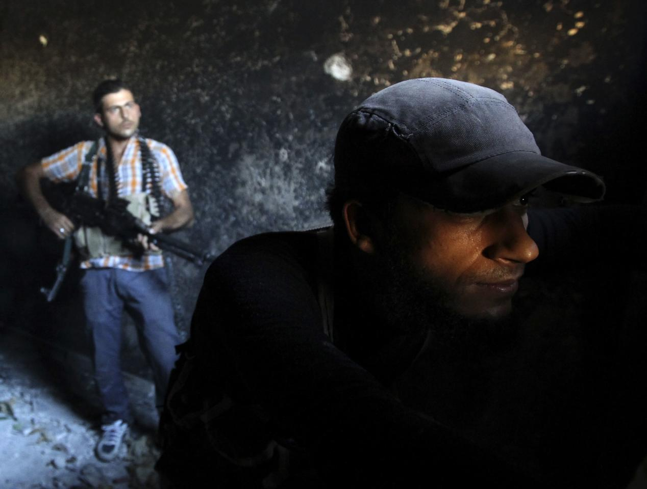 Free Syrian Army fighters take their shooting positions inside a house which was burnt in Ashrafieh, Aleppo September 20, 2013. REUTERS/Muzaffar Salman (SYRIA - Tags: POLITICS CIVIL UNREST CONFLICT TPX IMAGES OF THE DAY)