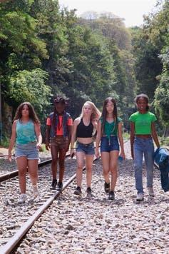 Five girls walk on train track over a gravel road.