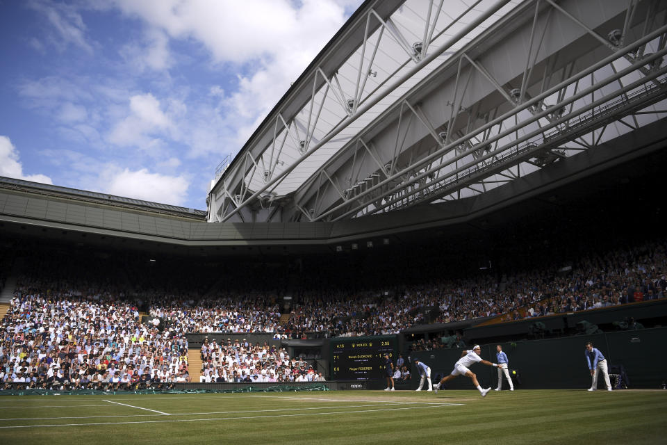 FILE - Switzerland's Roger Federer plays a return to Serbia's Novak Djokovic during the men's singles final match of the Wimbledon Tennis Championships in London, Sunday, July 14, 2019. The draw to set up the singles brackets for this year's Wimbledon will be held Friday, June 25, 2021. Play begins Monday.(Laurence Griffiths/Pool Photo via AP, File)
