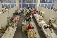 Patients with COVID-19 are seen in a hospital in Lviv, western Ukraine, Tuesday, March 23, 2021. Ukraine, which is struggling with a third wave of rising coronavirus infections, has recorded its highest daily death toll from COVID-19. (AP Photo/Evgeniy Maloletka)