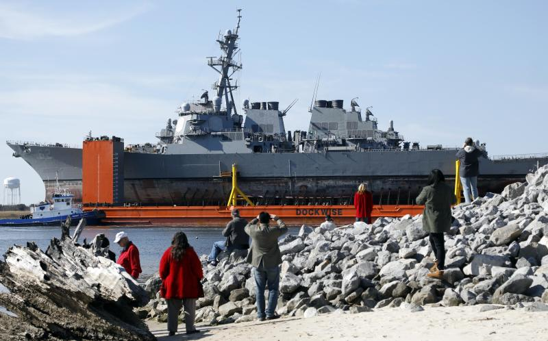 FILE - In this Jan. 19, 2018, file photo, area residents watch the transport vessel Transshelf carry the damaged USS Fitzgerald, the U.S. Navy destroyer damaged in a June 2017 collision off Japan, up the Pascagoula River in Pascagoula, Miss. Survivors and descendants of those killed when a container ship collided with the U.S. Navy destroyer off Japan's coast are suing the ship's Japanese charterer, according to a lawsuit filed Monday, Nov. 18, 2019, that details the survivors' scramble for safety as water rushed in. (AP Photo/Rogelio V. Solis, File)