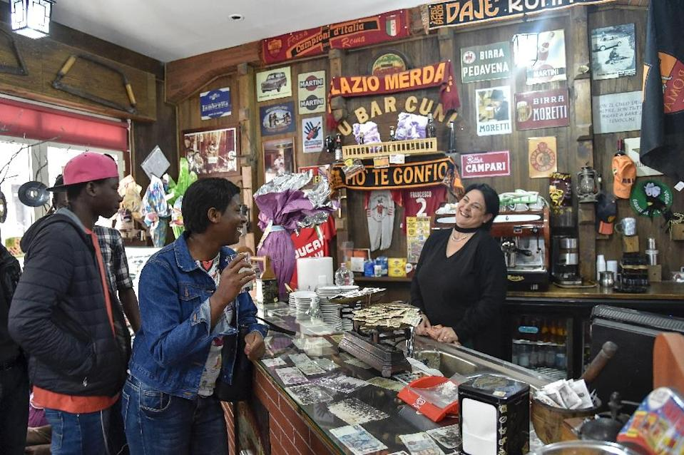 Migrants from Senegal and Niger joke with the waitress in the main bar of Sant' Alessio in Aspromonte, a small village of 330 inhabitants in Calabria, southern Italy (AFP Photo/Andreas Solaro)