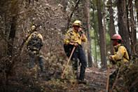 Firefighter hand crews take a break as they put out hot spots and mop up in an area burned in the Dixie Fire