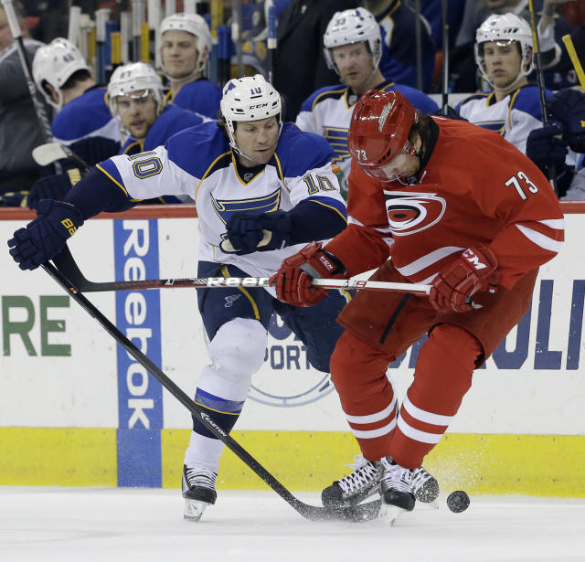 St. Louis Blues' Brenden Morrow (10) and Carolina Hurricanes' Brett Bellemore (73) chase the puck during the first period of an NHL hockey game in Raleigh, N.C., Friday, Jan. 31, 2014. (AP Photo/Gerry Broome)