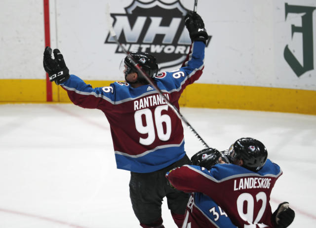 Colorado Avalanche right wing Mikko Rantanen (96) lifts up his arms in celebration after scoring in overtime against the Calgary Flames during Game 4 of an NHL hockey playoff series Wednesday, April 17, 2019, in Denver. Gabriel Landeskog (92) hugs Carl Soderberg (34). The Avalanche won 3-2. (AP Photo/David Zalubowski)