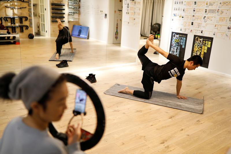 Trainer Wang Kai teaches a class that is being livestreamed at a gym, as the country is hit by an outbreak of the new coronavirus, in Beijing, China February 14, 2020. Picture taken February 14, 2020. REUTERS/Carlos Garcia Rawlins