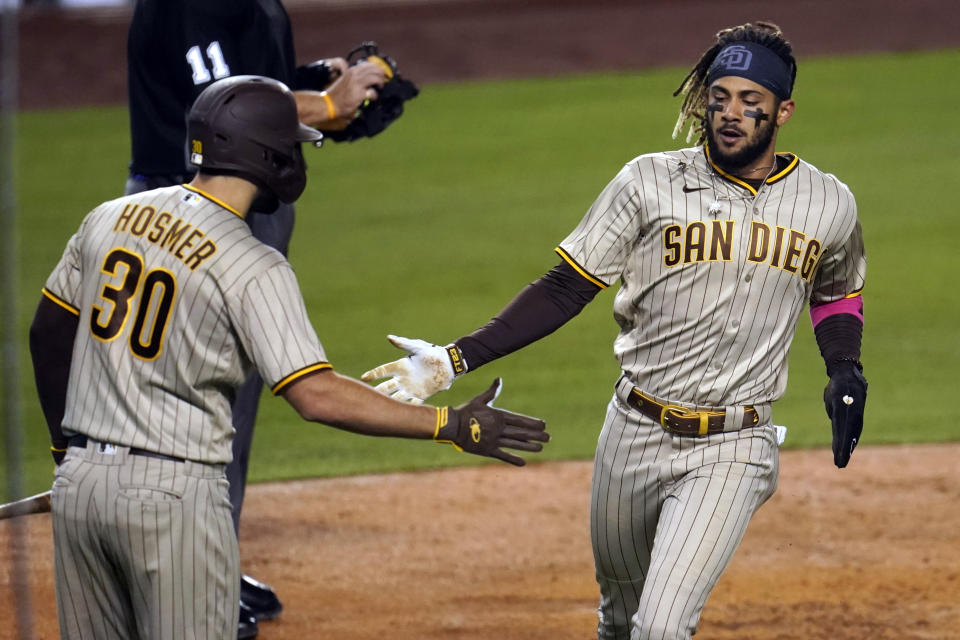 San Diego Padres' Fernando Tatis Jr., right, slaps hands with Eric Hosmer (30) after Tatis scored on single by Manny Machado during the fourth inning of a baseball game against the Los Angeles Dodgers on Thursday, April 22, 2021, in Los Angeles. (AP Photo/Marcio Jose Sanchez)